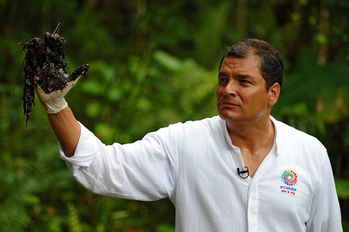 Ecuadorean President Rafael Correa shows his oil-covered hand at Aguarico 4 oil well in Aguarico, Ecuador on September 17, 2013. (AFP Photo / Rodrigo Buendia)