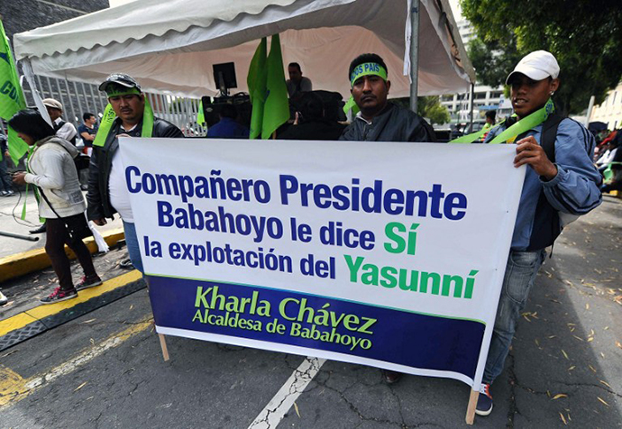 Supporters of President Rafael Correa, backing oil drilling in the Yasuni National Park, hold banners outside the National Assembly building in Quito on October 3, 2013, as lawmakers decide their vote on Correa's request for the exploitation. (AFP Photo / Rodrigo Buendia)