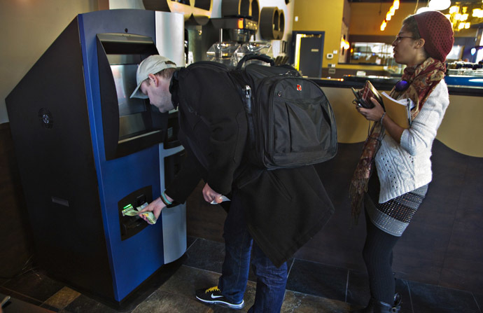 A customer puts money into the world's first ever permanent bitcoin ATM unveiled at a coffee shop in Vancouver, British Columbia October 29, 2013. (Reuters/Andy Clark)