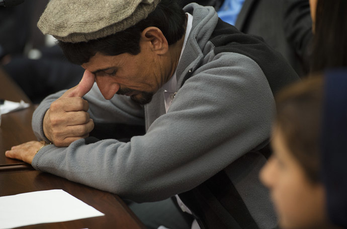 Rafiq ur Rehman takes a moment after speaking about the US drone strike in Pakistan that killed his mother and injured his daughter Nabila Rehman (R), 9,during a press conference on Capitol Hill in Washington, DC, October 29, 2013. (AFP Photo/Jim Watson)