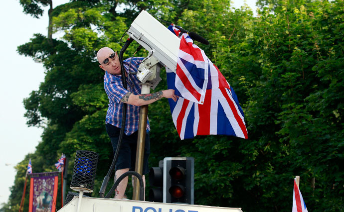 A man covers a surveillance camera with a Union flag after climbing on top of an armoured police Land Rover.(Reuters / Cathal McNaughton)
