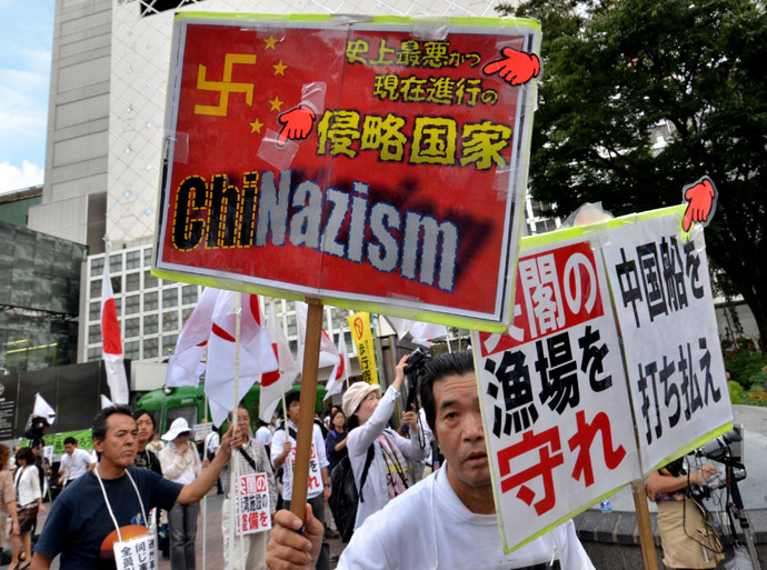 Japanese nationalists carry national flags and placards during a rally over the Senkaku islands issue, known as the Diaoyu islands in China, in Tokyo on September 18, 2012. (AFP Photo/Yoshikazu Tsuno)
