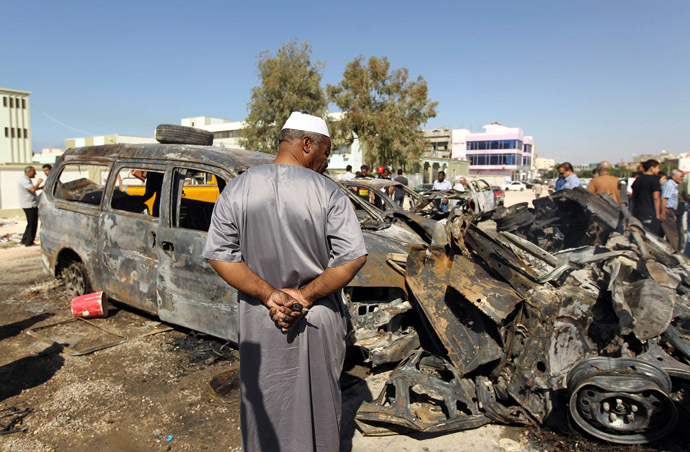 Benghazi residents gather at the site of a car blast in the parking lot of school used as an electoral office on October 26, 2013. (AFP Photo)