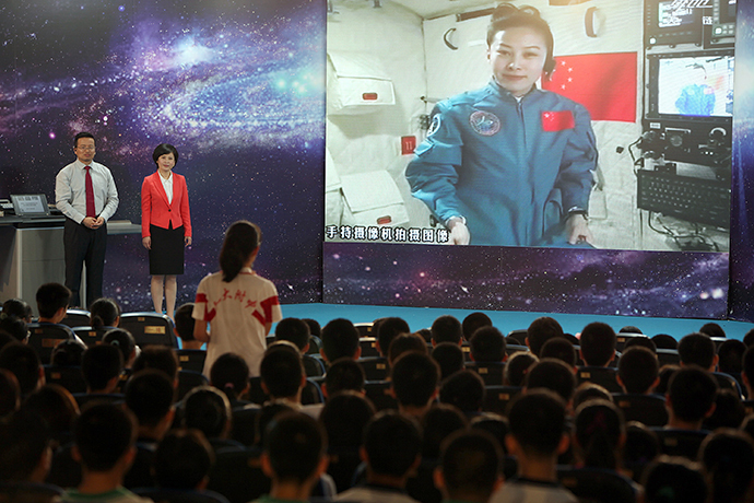 A girl in a school in Beijing asks Chinese female astrounaut Wang Yaping (Top R) questions as Wang delivers a lesson to students from Tiangong-1 space module in the morning of June 20, 2013. (AFP Photo)
