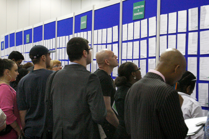 People look at job listings at the Careers and Jobs Live careers fair at the ExCeL centre in London (Reuters / Luke MacGregor)