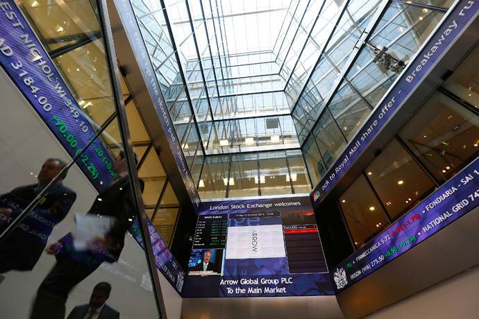 People pass electronic information boards at the London Stock Exchange in the City of London (Reuters / Stefan Wermuth)