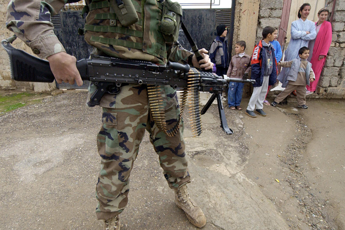 Iraqi children look at US soldiers from the 1st battalion, 22nd Regiment of the 4th Infantry Division conducting a foot-patrol along a street of former Iraqi dictator Saddam Hussein's hometown Tikrit, 180 Kilometers (110 miles) north of Iraqi capital Baghdad, 27 December 2003 (AFP Photo / Jewel Samad)