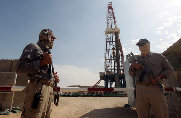 Gazprom security men stand guard in front of a drilling platform at an oilfield near the Iraqi city of Badra, south of Baghdad, on October 18, 2012. (AFP Photo)