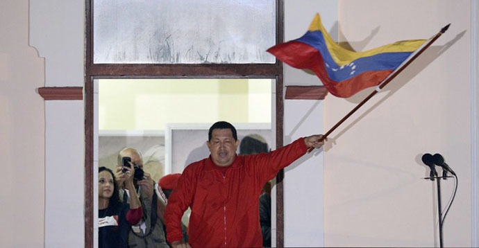 Venezuelan President Hugo Chavez waves a Venezuelan flag while speaking to supporters after receiving news of his reelection in Caracas on October 7, 2012. (AFP Photo / Juan Barreto)