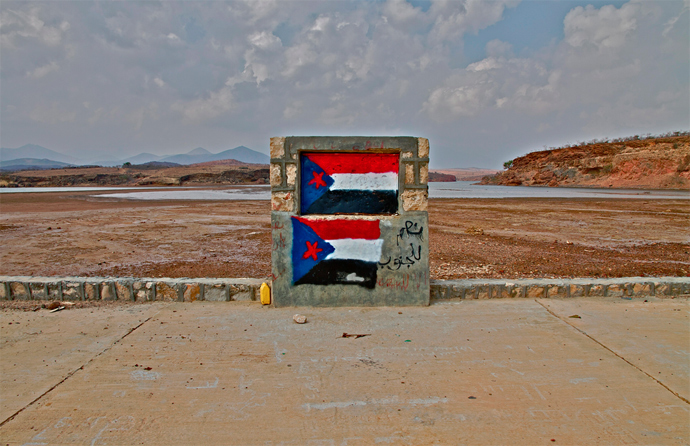 "The flag of the former South Yemen republic painted on a roadside with slogans reading, ""Yes to the South!"" (Photo by Nile Bowie)"
