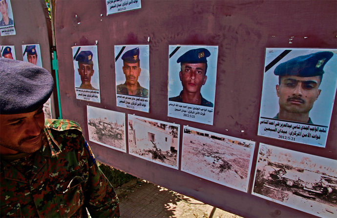 A Yemeni solider examines photographs of victims of a suicide bombing carried out by AQAP at a military parade rehearsal in Yemen's capital in May 2012. (Photo by Nile Bowie)