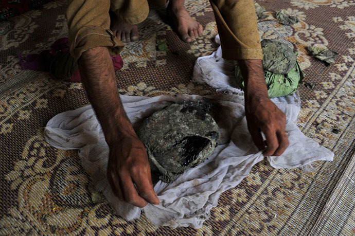 An Afghan man wraps a package of opium after harvesting from his poppy field in Pachir district of Nangarhar province (AFP Photo / Noorullah Shirzada)