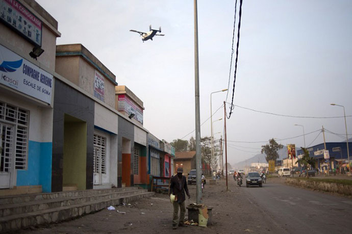 A man stands in a street as an aircraft comes in to land in Goma in the east of the Democratic Republic of the Congo on August 1, 2013 (AFP Photo/Phil Moore)