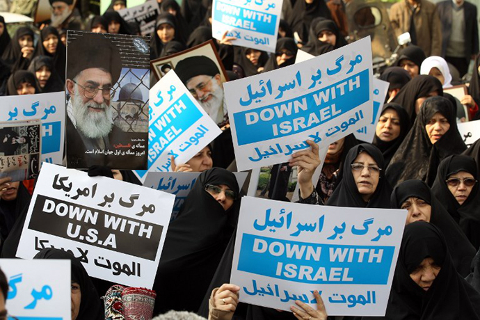 Iranians hold portraits of the Islamic republic's supreme leader, Ayatollah Ali Khamenei, and anti-Israel placards during a protest on November 16, 2012. (AFP Photo)