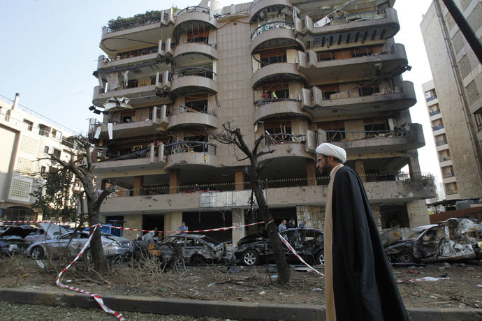 A Shiite cleric walks past a damaged building on November 20, 2013 at the scene of the previous day's double suicide bombing outside the Iranian embassy in Beirut in which at least 23 people were killed.(AFP Photo / Anwar Amro)
