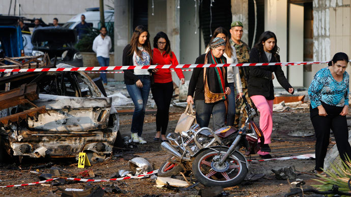 Lebanese onlookers walk on the site of a double suicide bombing outside Iran's embassy in Bir Hassan neighbourhood in southern Beirut on November 19, 2013.(AFP Photo / STR)