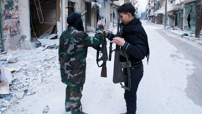 A female fighter in the Free Syrian Army exchanges her weapon with a fellow fighter in Aleppo's Salaheddine neighbourhood November 6, 2013. (Reuters / Mahmoud Hassano)