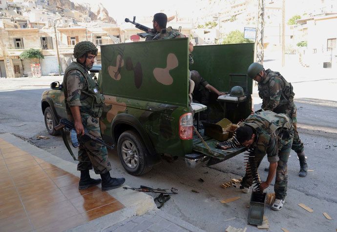 Syrian army forces load a machine gun mounted at the back of a vehicle in the Syrian Christian town of Maalula on Septamber 7, 2013.(AFP Photo / STR)