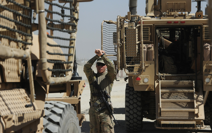 An US soldier from the 10th Mountain Division makes hand signals as Maxxpro Mine Resistant Ambush Protected vechiles prepare to leave on an operation at the Forward Operating Base Ghazni (AFP Photo / Dibyangshu Sarkar)