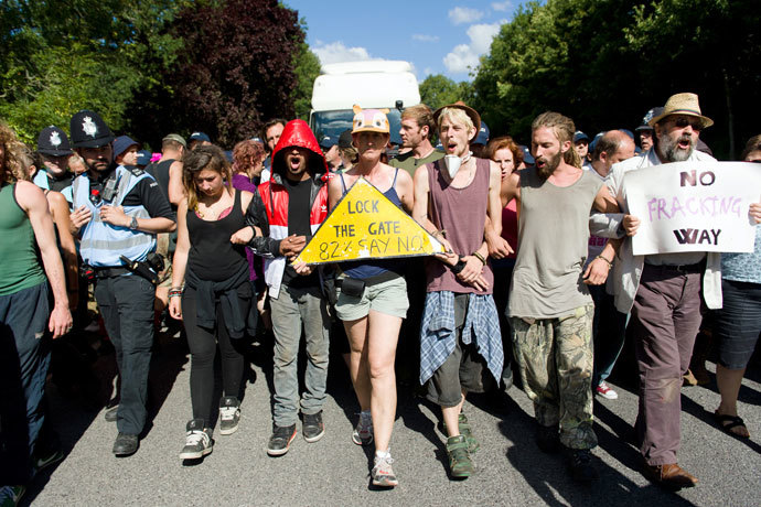 Climate and anti-fracking activists block the road in front of a tanker to delay its arrival to the test drill site operated by British energy firm Cuadrilla Resources in Balcombe, southern England, on August 20, 2013.(AFP Photo / Leon Neal)