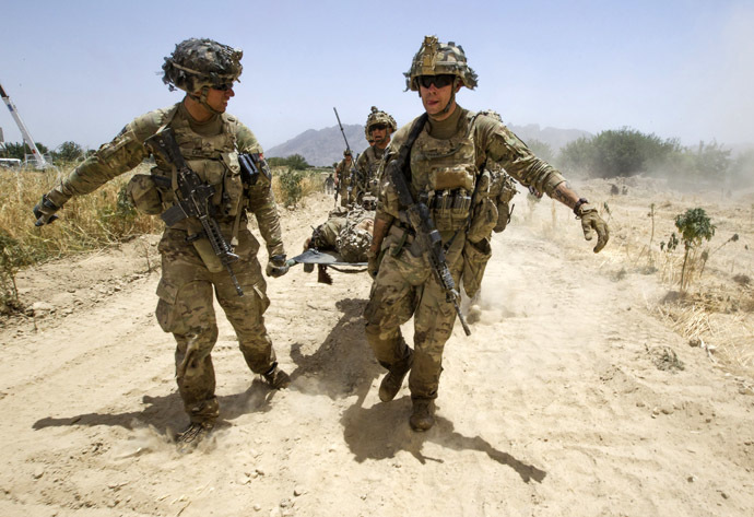 U.S. Army soldiers carry Sgt. Matt Krumwiede, who was wounded by an improvised explosive device (IED), towards a Blackhawk Medevac helicopter in southern Afghanistan June 12, 2012. (Reuters/Shamil Zhumatov)