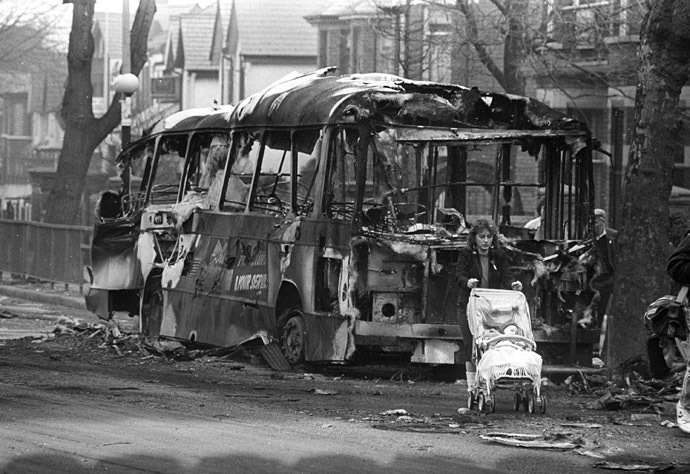 A woman pushes her baby carriage past a burnt bus in West Belfast set on fire March 16, 1988 after three people were killed by a gunfire and grenade attack during funerals for the IRA guerrillas killed in Gibraltar in this undated image. (Reuters)