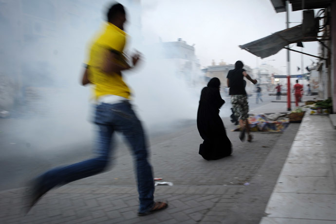 Bahraini Shiite Muslim protesters run for cover from tear gas fired by riot police during a clashes following a demonstration in solidarity with Bahraini Human Right Activist, Nabeel Rajab and against their government in the village of Malikiya, south of Manama (AFP Photo)