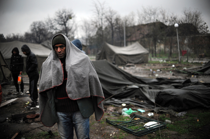 A man stands by 6 tents as snow falls in a refugee camp set in the Bulgarian town of Harmanli, south-east of Sofia, on November 27, 2013. Bulgaria's asylum centres are severely overcrowded after the arrival of almost 10,000 refugees this year, half of them Syrian (AFP Photo)