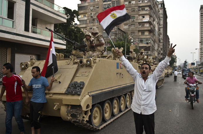 Egyptians salute Army tanks upon their deployment on a street leading to Cairo University on July 3, 2013 (AFP Photo / Khaled Desouki)