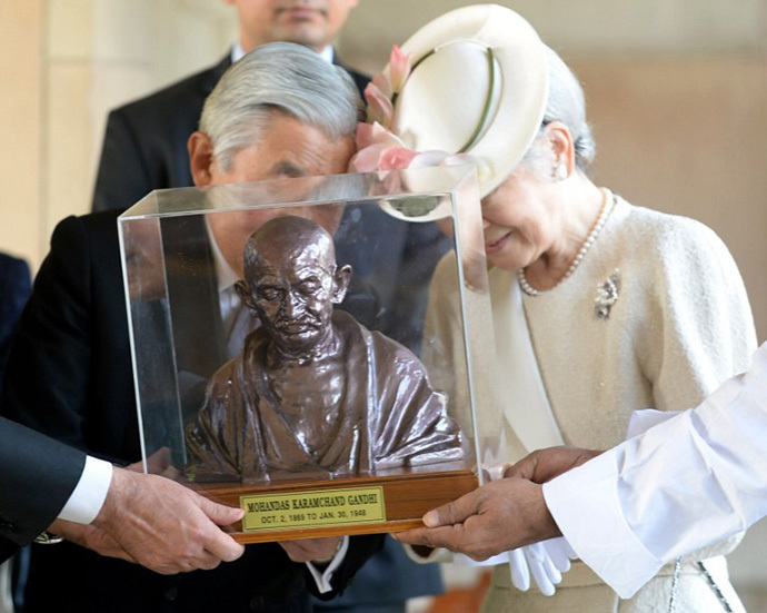 Japanese Emperor Akihito (C) and Empress Michiko (R) are assisted an unseen Indian External Affairs Minister Salman Khurshid as they receive a bust of Mahatma Gandhi from officials during a visit to Rajghat, the memorial to Mahatma Gandhi in New Delhi on December 2, 2013. (AFP Photo / Prakash Singh)