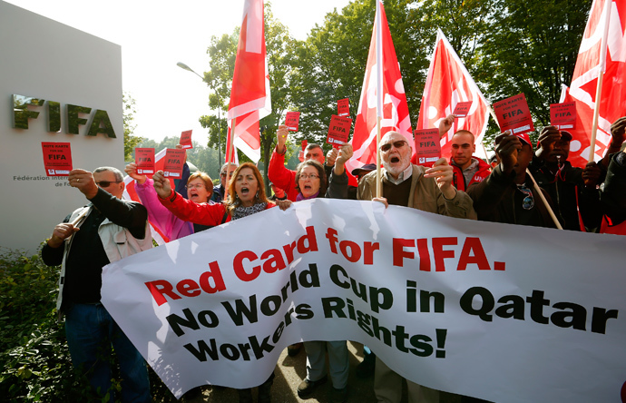 Members of the Swiss UNIA workers union display red cards and shout slogans during a protest in front of the headquarters of soccer's international governing body FIFA in Zurich (Reuters / Arnd Wiegmann)