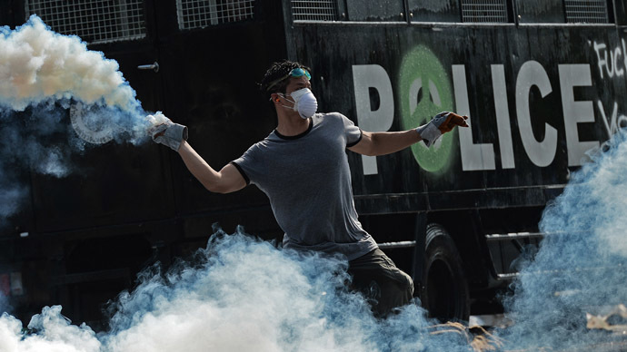 A Thai anti-government protester throws a tear gas canister back to the police during an ongoing rally outside Government House in Bangkok on December 2, 2013. (AFP Photo)