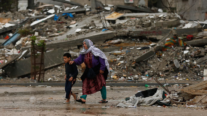 Palestinians walk near houses destroyed in a past Israeli air strike, on a windy winter day in Jabalya in the northern Gaza Strip.(Reuters / Mohammed Salem)
