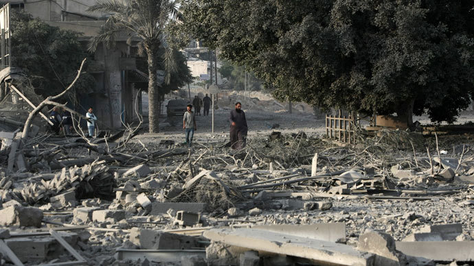 Palestinian men walk amidst debris at the destroyed compound of the internal security ministry in Gaza City after it was targeted by an Israeli air strike overnight.(AFP Photo / Mahmud Hams)