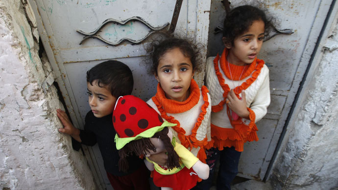 Palestinian children stand at the gate of their home as they watch the funeral procession of killed members of the Hejazi family, including two young children, in Beit Lahia, in the northern Gaza Strip.(AFP Photo / Mohammed Abed)