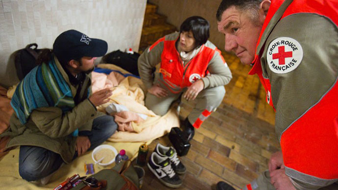 French Red Cross (Croix rouge) volunteers attend to a homeless person living in a train station tunnel (AFP Photo / Loic Venance)