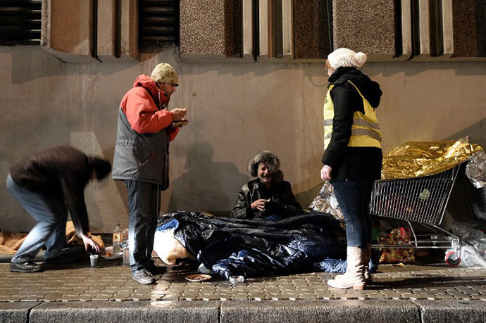 Volunteers of the French charity Les Restos du Coeur (Restaurants of the Heart) distribute on November 25, 2013 hot meals to homeless people in the streets of the eastern French city of Strasbourg. (AFP Photo / Frederic Florin)