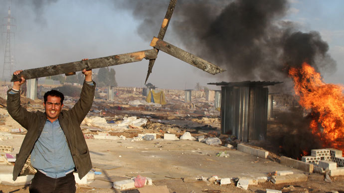 A man holds up a broken wooden structure in a burnt makeshift Syrian refugee camp after it was attacked by residents of the neighbouring eastern Lebanese village of Qsar Naba near Zahle in the Bekaa valley, on December 2, 2013. (AFP Photo / STR)