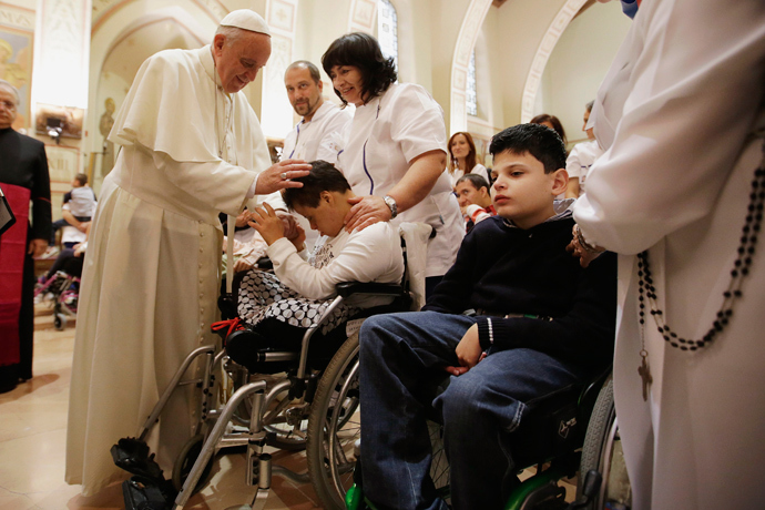 Pope Francis blesses a disabled person during his visit at the Serafico Institue in Assisi October 4, 2013. (Reuters / Gregorio Borgia / Pool)