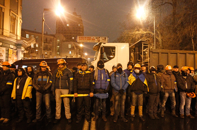 People wear helmets and masks as they line up during a rally organized by supporters of EU integration in central Kiev, December 8, 2013. (Reuters / Vasily Fedosenko)