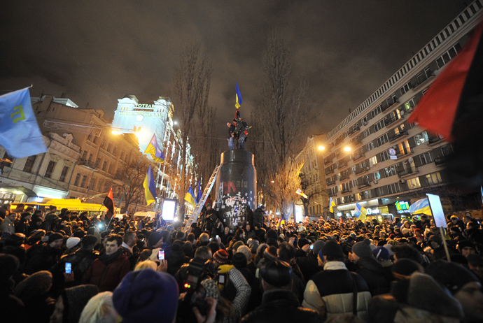 """Protesters celebrate after a statue of Lenin at a monument in his honor was pulled down and then destroyed during a mass rally called """"The March of a Million"""" in Kiev's Independence Square on December 8, 2013. (AFP Photo / Genya Saviov)"""