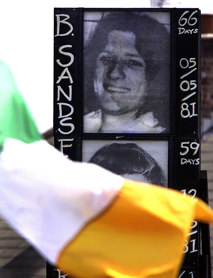 An Irish flag flutters in the wind May 3, 2001 in front of a picture of republican hunger striker, Bobby Sands, who died after 66 days on the hunger strike in the Maze twenty years ago tomorrow.(Reuters)