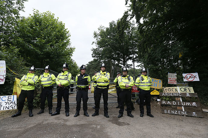 Police officers guard a gate on the edge of a site run by Cuadrilla Resources, near Balcombe in southern England August 16, 2013 (Reuters / Stefan Wermuth)