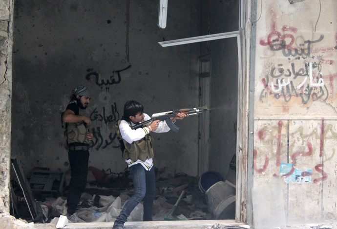 A rebel fighter from the Free Syrian Army fires his weapon during fighting against government forces in the Salah al-Din neighbourhood of the northern Syrian city of Aleppo. (AFP Photo / Mahmud Al-Halabi)