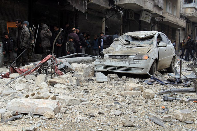 Syrians look at the bomb damage allegedly caused by pro-government forces in a neighborhood held by rebel forces in the northern city of Aleppo on December 16, 2013. (AFP Photo / Mohammed Al-Khatieb)