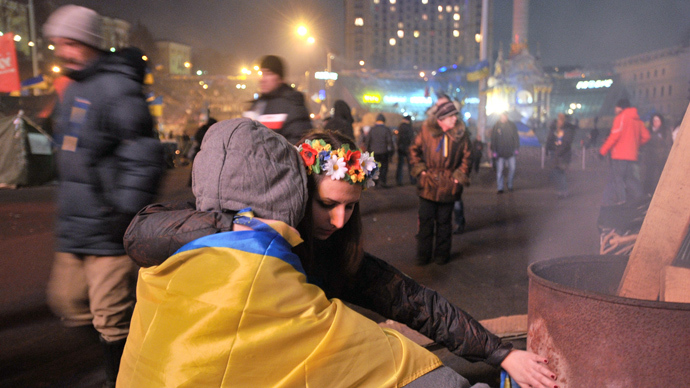 A couple warms its hands near a fire on Independence Square in Kiev late on December 17, 2013 (AFP Photo / Genya Savilov)