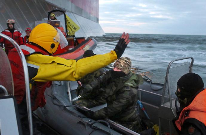 """Uma foto apostila feita pelo Greenpeace em 18 de setembro de 2013, mostra uma camuflagem vestidos com máscara oficial russo Guarda Costeira (C) apontando uma faca em um ativista do Greenpeace Internacional (L) durante a 'tentativa de subir da Gazprom """"uma ambientalistas petróleo do Ártico Prirazlomnaya' plataforma em algum lugar fora da Rússia costa norte-oriental, no Mar Pechora. (AFP Photo / Greenpeace / DenisSINYAKOV)"""