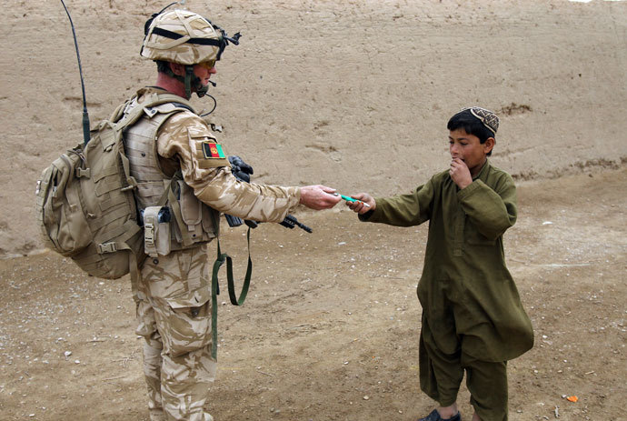 A British soldier of the 1st batallion of the Royal Welsh gives a pen to an Afghan boy during a patrol in the streets of Showal in Nad-e-Ali district, Southern Afghanistan.( AFP Photo / Thomas Coex)