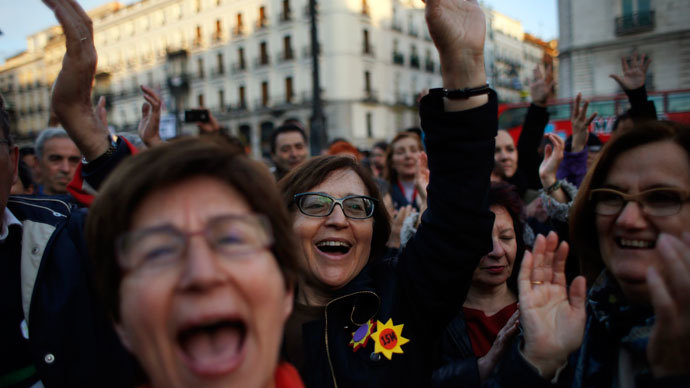 Demonstrators sing and raise their hands during a gathering to mark the second anniversary of the 15M movement at Madrid's landmark Puerta del Sol Square May 15, 2013.(Reuters / Susana Vera)