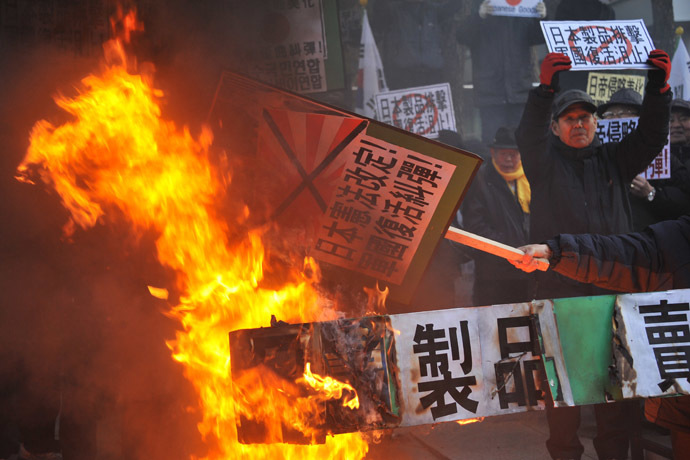 South Korean conservative activists set fire to effigies of Japanese Prime Minister Shinzo Abe during a protest to lodge a complaint against Abe visiting the Yasukuni war shrine to mark the first anniversary of his taking office, in Seoul on December 27, 2013. (AFP Photo/Woohae Cho)